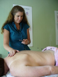 Acupuncturist performing acupuncture treatment.